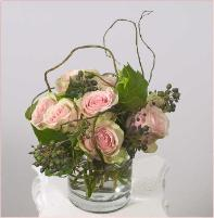 Rose design with curly willow glass vase on desktop